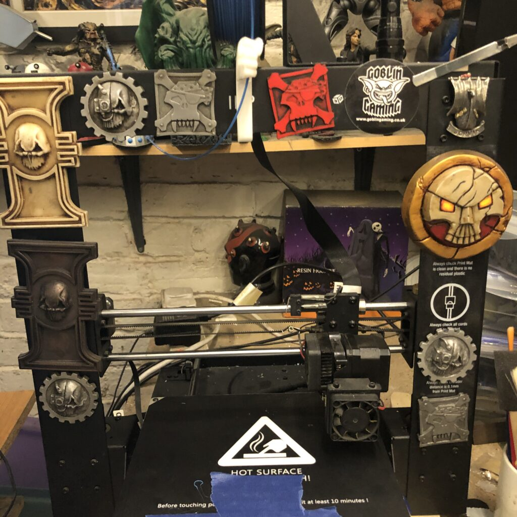 A 3d printer with ork, inquisition and adeptus mechanicus symbols